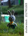 Stock photo handmade knitted toy hare amigurumi rabbit on the nature background funny hare in green pants 1517901005