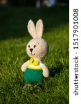 Stock photo handmade knitted toy hare amigurumi rabbit on the nature background funny hare in green pants 1517901008