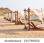 Row of luxurious beds on beach resort - stock photo