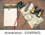 Small photo of Vintage binoculars, notepad, compass, old map, ink pen, inkwell, pocket knife, magnifying glass on wooden background
