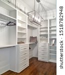 Small photo of new modern white master bedroom closet with shelving and nobody display