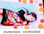 Small photo of Young woman relaxing in Spa bath with slices of oranges. Welness concept.