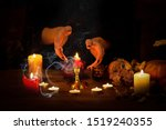 Small photo of Witch guessing on wax on the altar in the dark. Female hands with sharp black nails making passes above candles, pumpkin, nuts, dry leaves, magic herbs, selected focus, low key. Halloween, Yule