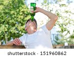Small photo of Man with a severe drinking problem upending a bottle of spirits and gulping down the alcohol as he sits outdoors under leafy green trees