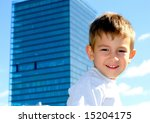 Smiling toddler in front of a big office building - stock photo
