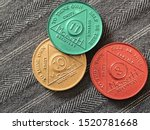 Small photo of Guadalajara, Mexico - September 9 2019: AA Sobriety chips awarded from abstaining from alcohol or other substance for 8, 10, 11 months. It is a token given to 12 step group members. Successful rehab