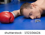 Small photo of Defeated boxer. Close-up of defeated boxer lying down on the boxing ring with closed eyes