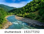 river with rocky beach at the foot of the mountain - stock photo