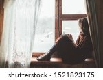 Small photo of Pre teen child in warm woolen sweater seating on window sill and reading a book. Winter weekends in old log house. Cold snowy weather. Cozy homely concept.