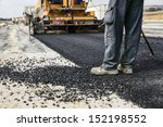 Worker Operating Asphalt Paver...
