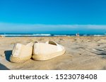 Stock photo lost espadrilles on the sand on a sunny summer day at the beach 1523078408