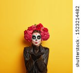 Small photo of Portrait of female zombie with painted skull face, sends air kiss, expresses love, celebrates day of death, prays for family members who died comes on Mexican holiday or festival has halloween makeup