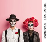 Small photo of Lovely couple wear zombie costume for Halloween, have skull makeup, man wears hat and white shirt with red rose in pocket, woman in black leather jacket and flower wreath, wait for party together