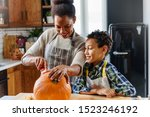 Mother And Son Carving Pumpkin...