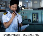 Asian chief, marine navigational officer is reporting by VHF radio during navigation watch. Bridge GMDSS watch.