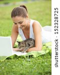 Stock photo beautiful girl with her kitty and laptop outdoors 152328725