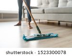 Small photo of Woman housewife wash wooden laminate floor in modern living room, female cleaner housekeeper maid holding mop cleaning at home, domestic housework professional household service concept close up view