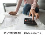 Small photo of Woman renter holding paper bills using calculator for business financial accounting calculate money bank loan rent payments manage expenses finances taxes doing paperwork concept, close up view