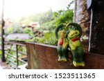 Two Frog Statues On A Wooden...