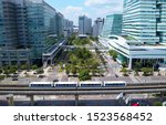 Aerial view of a green open space surrounded by modern office buildings and a metro train traveling on the elevated rails of Wenhu MRT line on a sunny day, in Nankang Software Park, Taipei, Taiwan