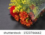 Small photo of Bouquet wrapped in cellophane on black background