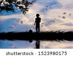 Stock photo silhouette the girl walks with his dog in the morning at lawn 1523980175