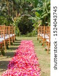 Round wedding arch in Boho style for a ceremony decorated with fresh greenery and flowers. Tiffany chairs and pink and red petal aisle. Concept of a tropical wedding. Bali, Indonesia.