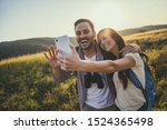 Happy couple is hiking in mountain. They are taking selfie. - stock photo