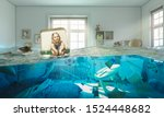 Small photo of 3 year old blond girl sitting inside a vintage suitcase floats on water in her flooded bedroom. Concept of difficulty and carefree.