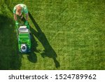 Lawn Moving Aerial Photo. Caucasian Gardener with Gasoline Grass Mower at Work. Landscaping Business. Industrial Theme. - stock photo