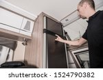 RV Motorhome Refrigerator Check by the Owner. Preparing Recreational Vehicle For the Season. Travel Trailer Interior. - stock photo