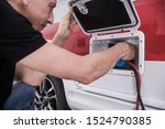 Motorhome Electric Exterior Hookup. RV Recreational Vehicle Owner Plugging in Electricity.  - stock photo