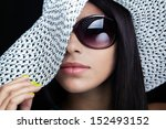 Close-up portrait of a beautiful young woman with sunglasses and white hat - stock photo