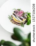 Stock photo appetizer food salted herring butter and red onion on white plate selective focus vertical view 1527106208