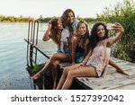 Small photo of Group of females sitting on a pier together on a weekend breakaway and taking selfie