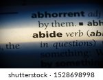 Small photo of abide word in a dictionary. abide concept, definition.