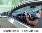 Small photo of woman driving a car, in summer and autumn outside city in forest, looks in rear view mirror, reversing, parking car, looks out window, gives back