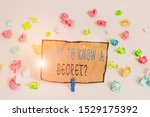 Small photo of Text sign showing Want To Know A Secret Question. Conceptual photo to divulge a confidential vital information Colored crumpled papers empty reminder white floor background clothespin.