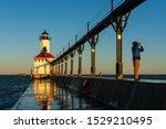 Man with binoculars as the sun rises at Michigan City Lighthouse.