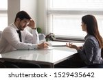 Small photo of Confused male hr manager listening to female job applicant at interview. Young woman making bad first impression on doubtful company recruiter. Employer unsure about working experience of candidate.