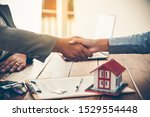 Small photo of Real estate agents and Clients join hands to congratulate them on achieving contractual agreements, regarding insurance, done business deal for transfer right of property.