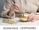 An Elderly Woman Paints A...
