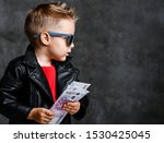 Small photo of Portrait of serious-looking rich kid boy in leather jacket with a bundle of money euro cash is interested in something on free copy space near him on concrete wall background