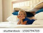 Small photo of Little cute girl built impromptu fort (castle, house) out of pillows and blankets on bed. Children handmade tent lodge.