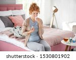 Small photo of Applying nasal spray. Red-haired woman sitting on bed and applying nasal spray because of stuffy nose