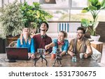 Young millenial friends sharing creative content online - Digital marketing concept with next generation influencer having fun on air with radio video stream - Vlogging time at startup coworking space - stock photo