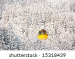 Yellow cable car in a winter landscape - stock photo