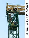 Small photo of a fragment of a gantry crane with a crane operator's cabin against the sky