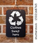 Small photo of Clothes Swap here text and symbol on chalk board, sustainable fashion and zero waste, recycle clothes and textiles to reduce waste