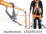 Construction worker wearing safety harness and safety line working at high place. Working at height equipment. Fall arrestor device for worker with hooks for safety body harness - stock photo